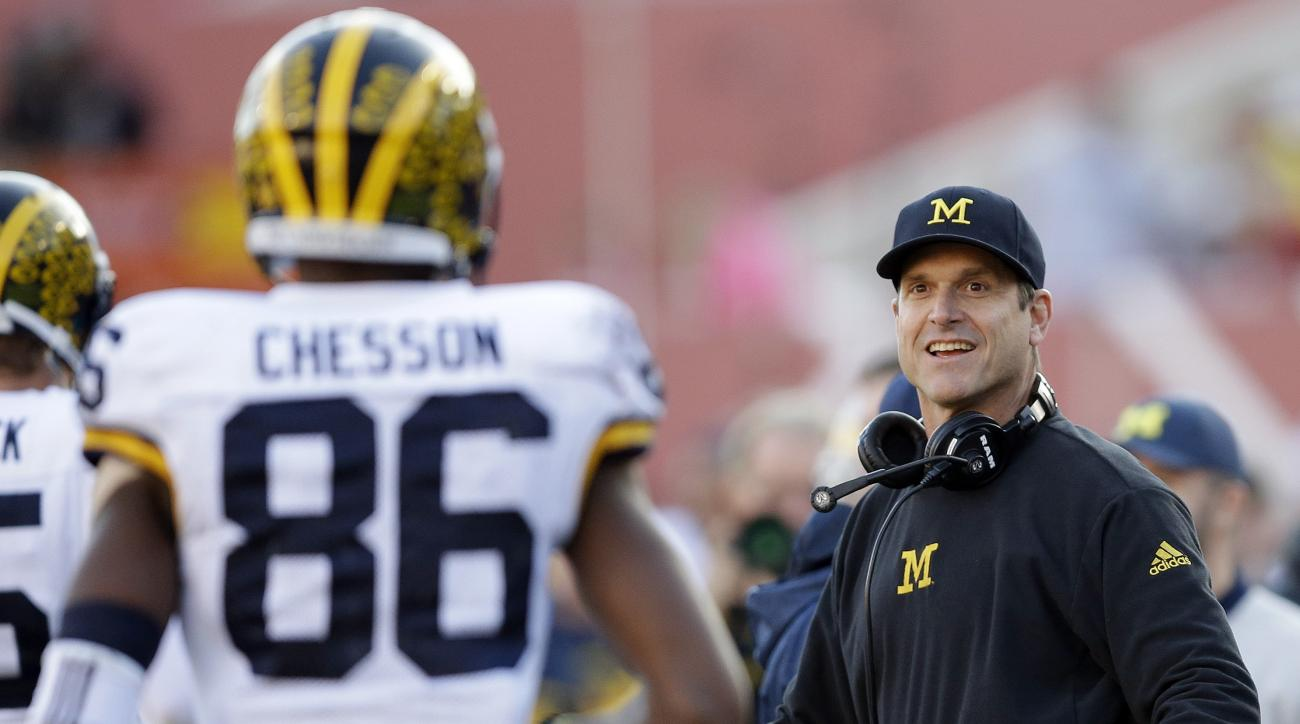 FILE - In this Nov. 14, 2015, file photo, Michigan head coach Jim Harbaugh congratulates Jehu Chesson (86) after Chesson caught a touchdown pass during the first half of an NCAA college football game against Indiana, in Bloomington, Ind. Most of the forme