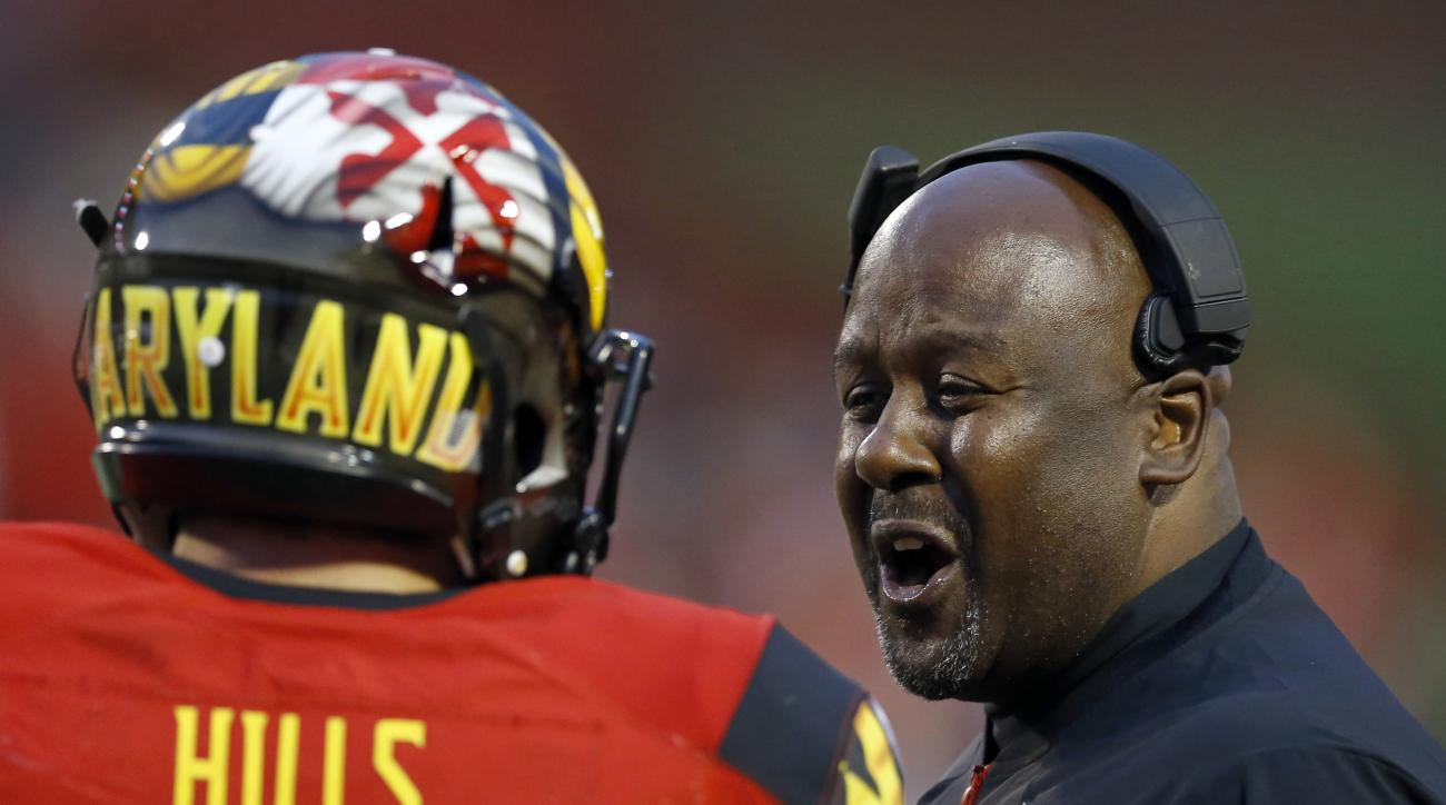FILE - In this Nov. 7, 2015, file photo, Maryland interim head coach Mike Locksley, right, speaks with quarterback Perry Hills on the sideline in the first half of an NCAA college football game against Wisconsin, in College Park, Md. Indiana and Maryland