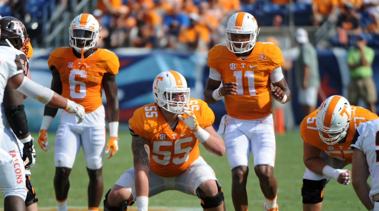 In this Sept. 5, 2015, photo, Tennessee center Coleman Thomas gets set for a snap to quarterback Joshua Dobbs during a NCAA football game against Bowling Green, in Nashville, Tenn. Injuries have forced Tennessee to use various combinations on the offensiv