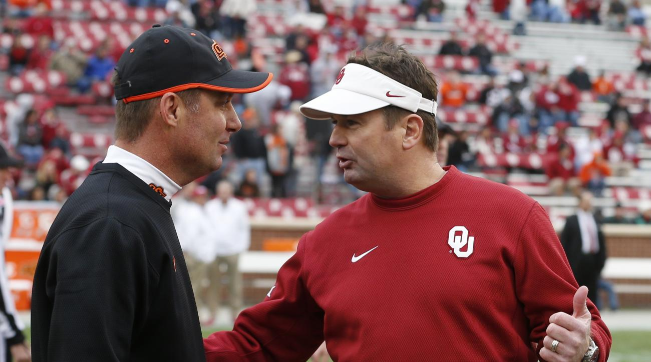FILE - In this Dec. 6, 2014, file photo, Oklahoma State head coach Mike Gundy, left, talks with Oklahoma head coach Bob Stoops, right, before the start of an NCAA college football game in Norman, Okla. Oklahoma State's Mike Gundy and Oklahoma's Bob Stoops