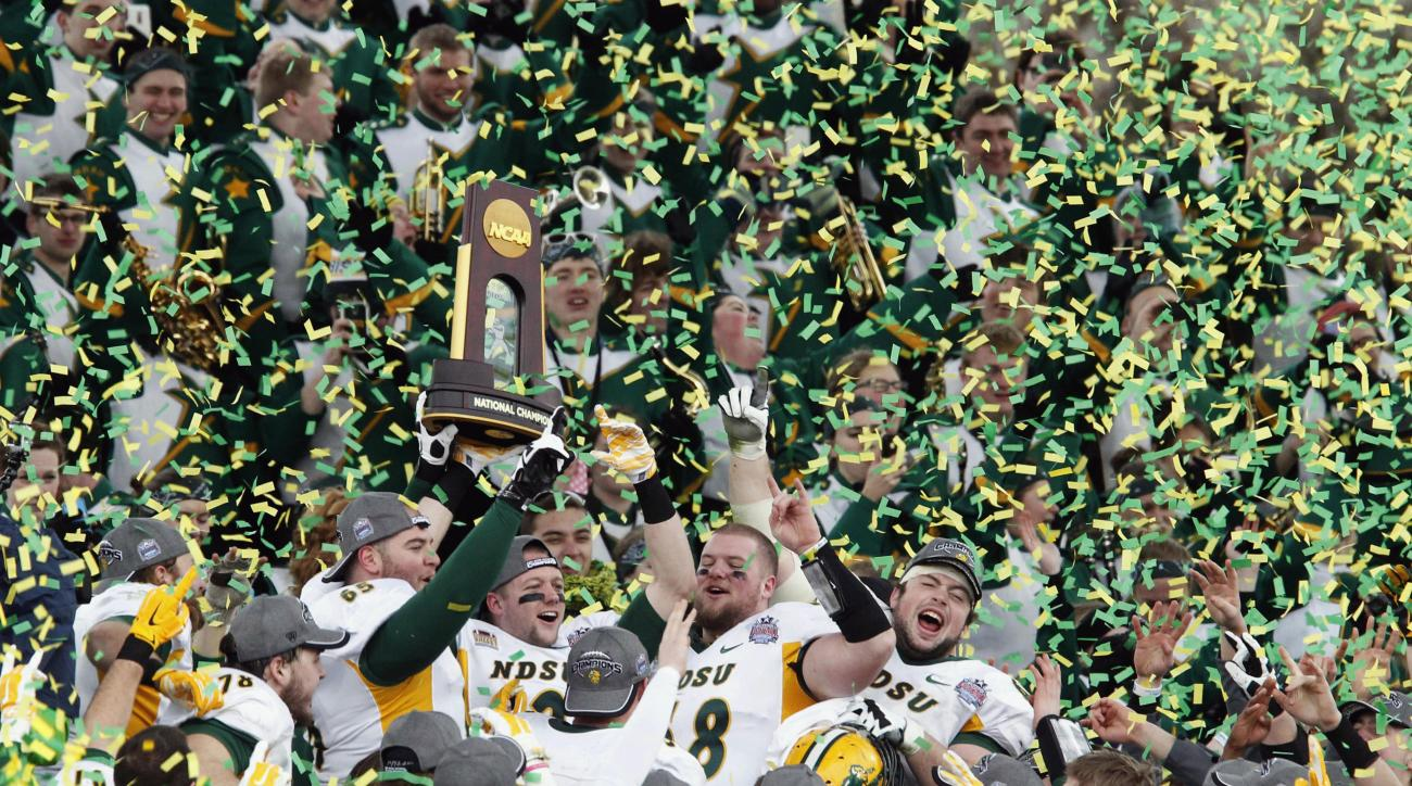 FILE - In this Jan. 10, 2015,  file photo, members of the North Dakota State football team hold the championship trophy after their 29-27 win over Illinois State in the FCS Championship NCAA college football game in Frisco, Texas. When North Dakota State