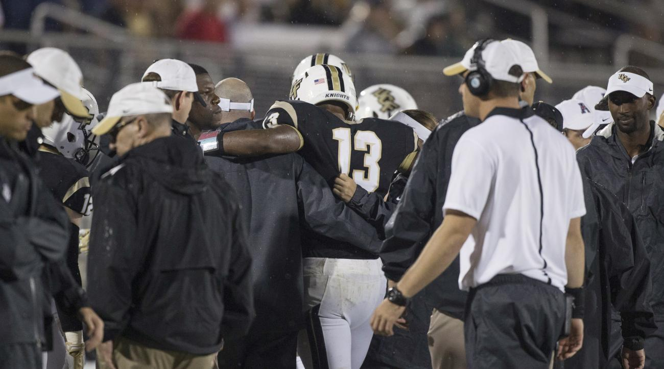 Central Florida quarterback Justin Holman (13) is helped off the field during the first half of an NCAA college football game  against East Carolina on Thursday, Nov. 19, 2015, in Orlando, Fla. (AP Photo/Willie J. Allen Jr.)