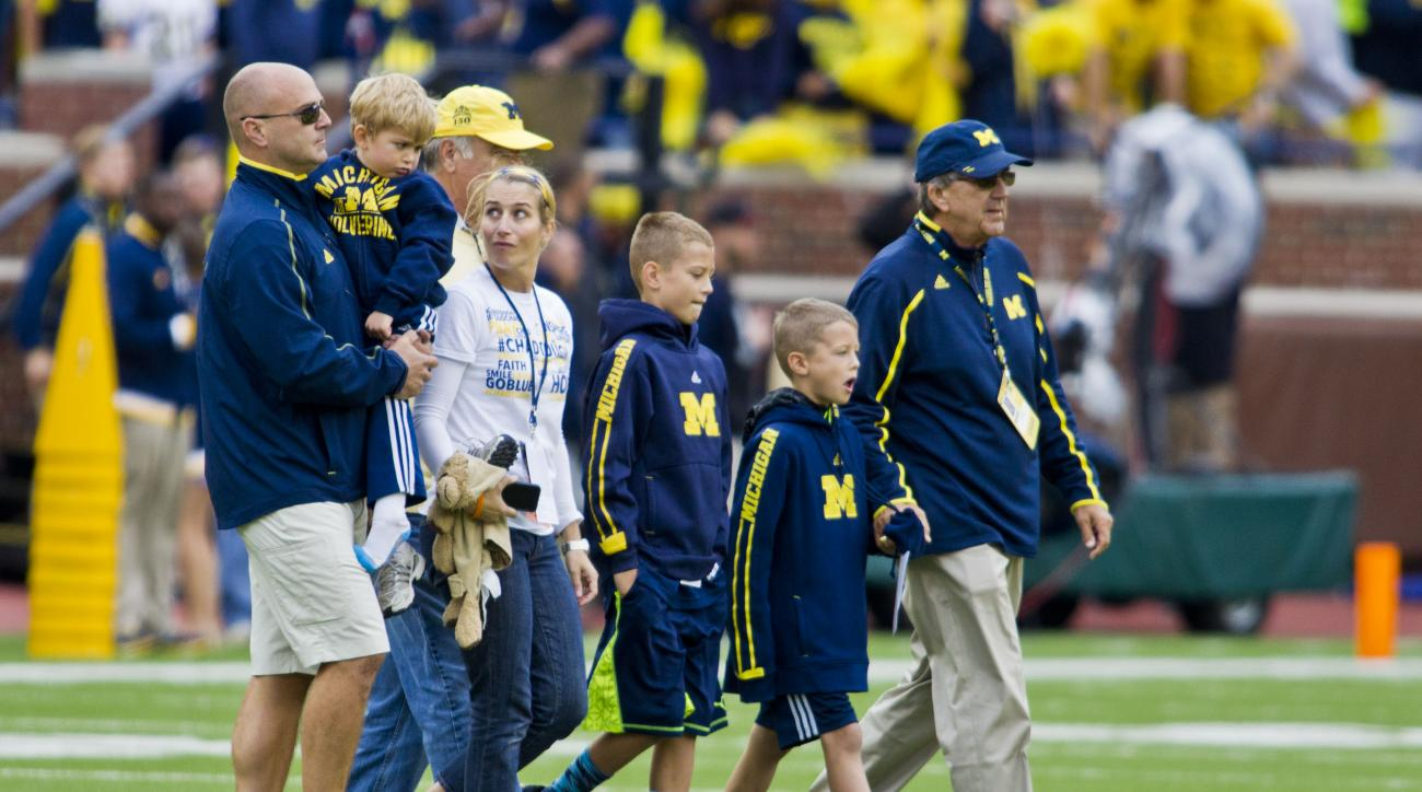 FILE - In this Sept. 12, 2015, file photo, former Michigan coach Lloyd Carr, far right, leads his grandsons T.J. and Tommy Carr, daughter-in-law Tammi Carr, and son Jason Carr, far left, holding his son Chad Carr, onto the Michigan Stadium field for the p
