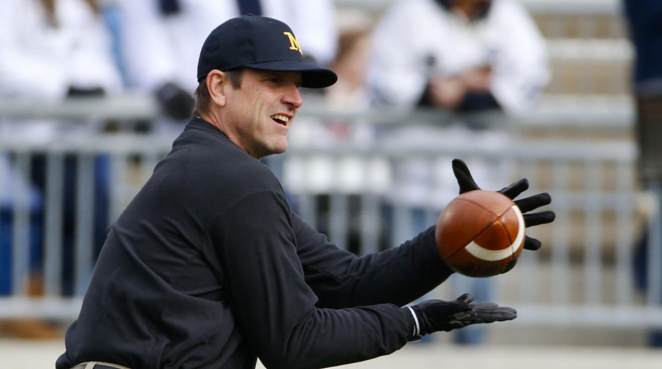 Michigan head coach Jim Harbaugh catches passes as he warms up his quarterbacks before an NCAA college football game in State College, Pa., Saturday, Nov. 21, 2015. (AP Photo/Gene J. Puskar)