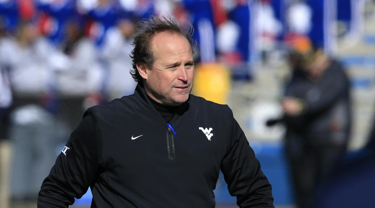 West Virginia head coach Dana Holgorsen walks the sidelines during the first half of an NCAA college football game against Kansas in Lawrence, Kan., Saturday, Nov. 21, 2015. (AP Photo/Orlin Wagner)