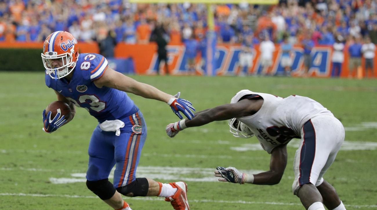 Florida tight end Jake McGee, left, slips past Florida Atlantic defensive back Alfred Ansley after a reception to score the winning touchdown on a 13-yard pass play during overtime to give Florida a 20-14 victory in an NCAA college football game, Saturday