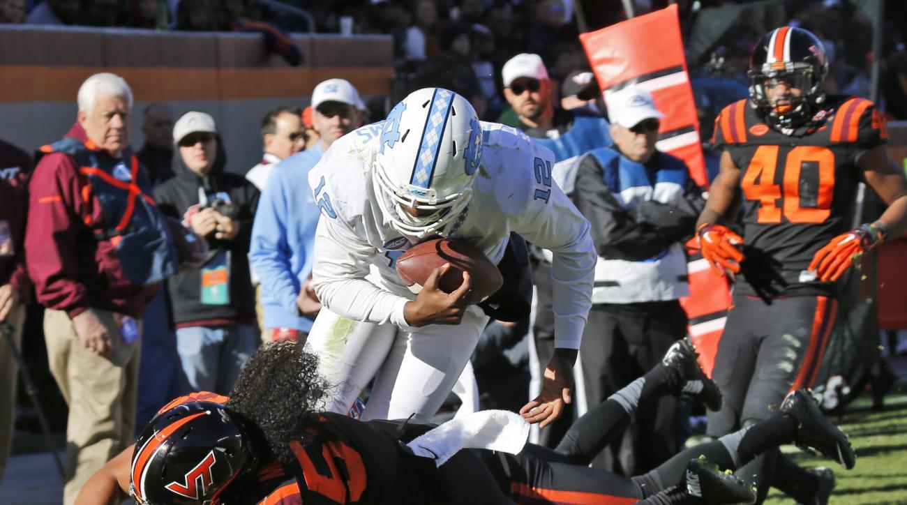 North Carolina quarterback Marquise Williams (12) dives toward the end zone as Virginia Tech linebacker Andrew Motuapuaka (54) defends during the second half of an NCAA college football game in Blacksburg, Va., Saturday, Nov. 21, 2015.  Williams was short
