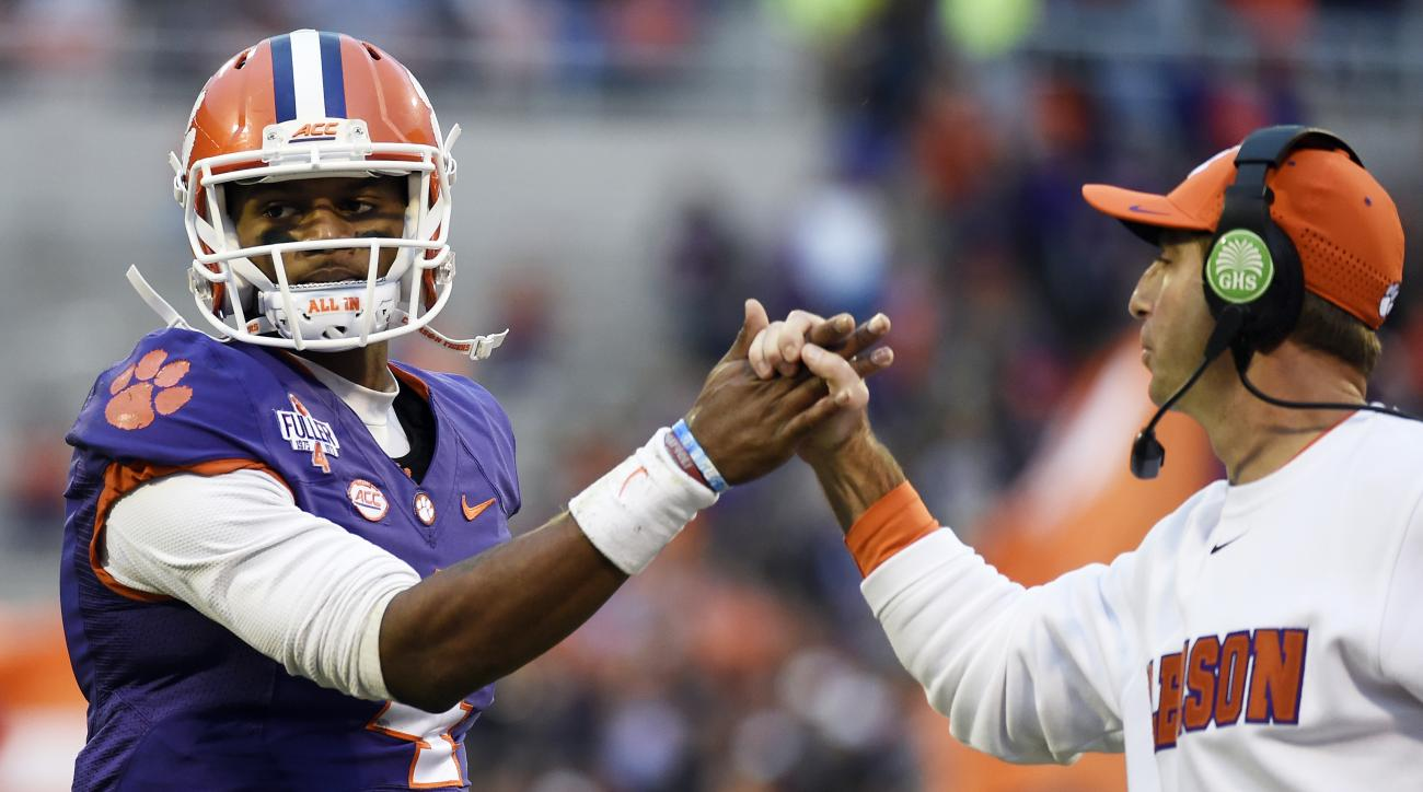 Clemson quarterback Deshaun Watson, left, is congratulated by head coach Dabo Swinney, after throwing a touchdown pass during the first half of an NCAA college football game against Wake Forest on Saturday, Nov. 21, 2015, in Clemson, S.C. (AP Photo/Rainie