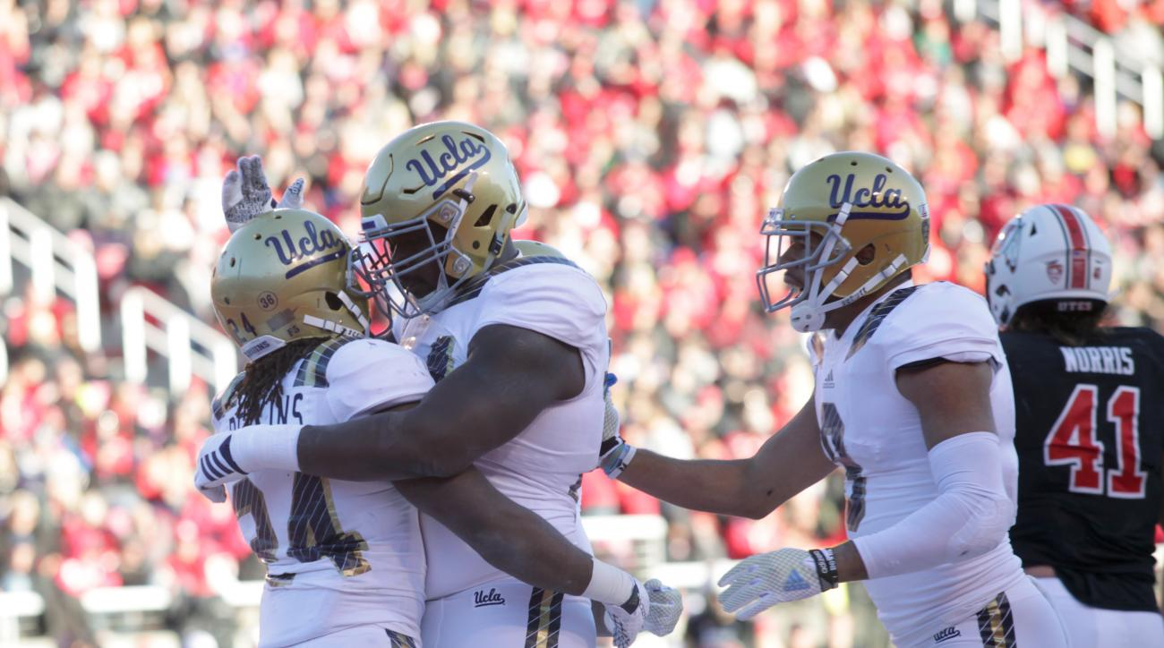 UCLA defensive back Denzel Fisher, left, celebrates scoring a touchdown with UCLA offensive lineman Caleb Benenoch, middle, in the second half of an NCAA college football game on Saturday, Nov. 21, 2015 in Salt Lake City. UCLA won the game 17-9. (AP Photo