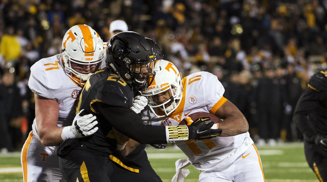 Tennessee quarterback Joshua Dobbs, right, pushes past Missouri's Donavin Newsom center, as Dylan Wiesman, left, blocks as Dobbs scores a touchdown during the first half of an NCAA college football game Saturday, Nov. 21, 2015, in Columbia, Mo. (AP Photo/