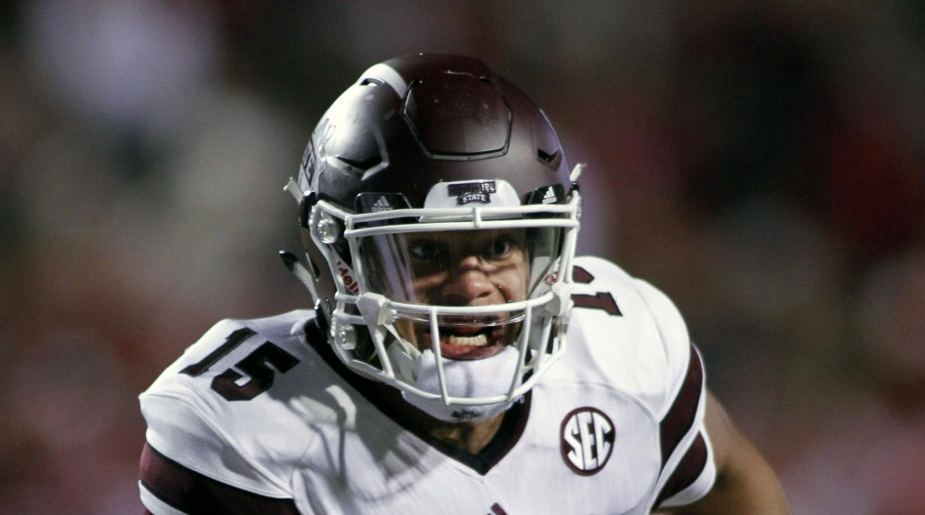 Mississippi State's Dak Prescott (15) keep the ball and runs during the the first half of an NCAA college football game against Arkansas, Saturday, Nov. 21, 2015 in Fayetteville, Ark. (AP Photo/Samantha Baker)
