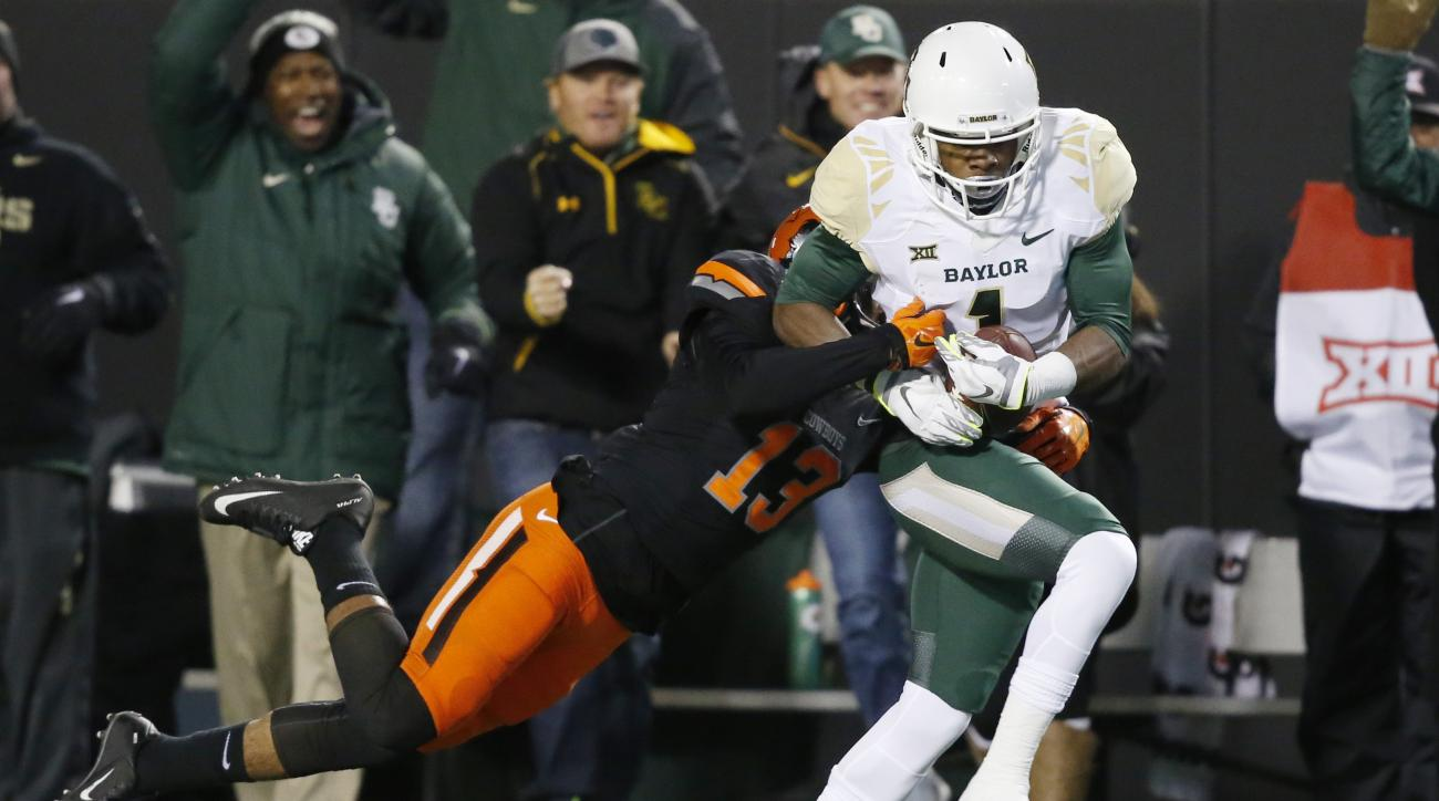 Baylor wide receiver Corey Coleman (1) is tackled by Oklahoma State safety Jordan Sterns (13) in the first quarter of an NCAA college football game in Stillwater, Okla., Saturday, Nov. 21, 2015. (AP Photo/Sue Ogrocki)