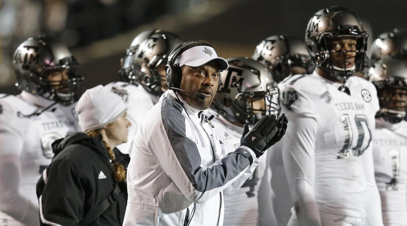 Texas A&M head coach Kevin Sumlin, center, watches a replay on the scoreboard in the first half of an NCAA college football game against Vanderbilt, Saturday, Nov. 21, 2015, in Nashville, Tenn. (AP Photo/Mark Humphrey)