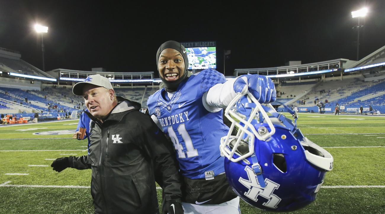Kentucky linebacker Josh Allen celebrates with head coach Mark Stoops as they leave the field after defeating Charlotte 58-10 in an NCAA college football game Saturday, Nov. 21, 2015, in Lexington, Ky. (AP Photo/David Stephenson)