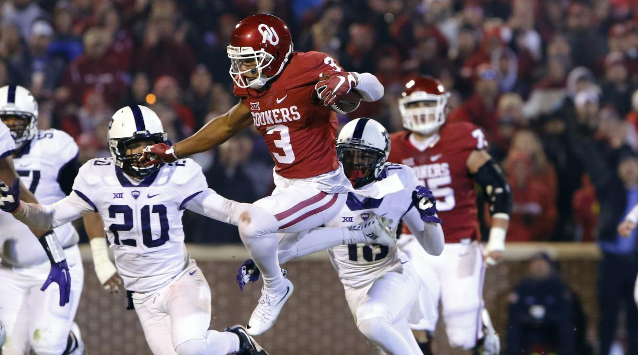 Oklahoma wide receiver Sterling Shepard (3) leaps to avoid as TCU linebacker Montrel Wilson (20) and others chase him during the third quarter of an NCAA college football game in Norman, Okla., Saturday, Nov. 21, 2015. Oklahoma won 30-29. (AP Photo/Alonzo