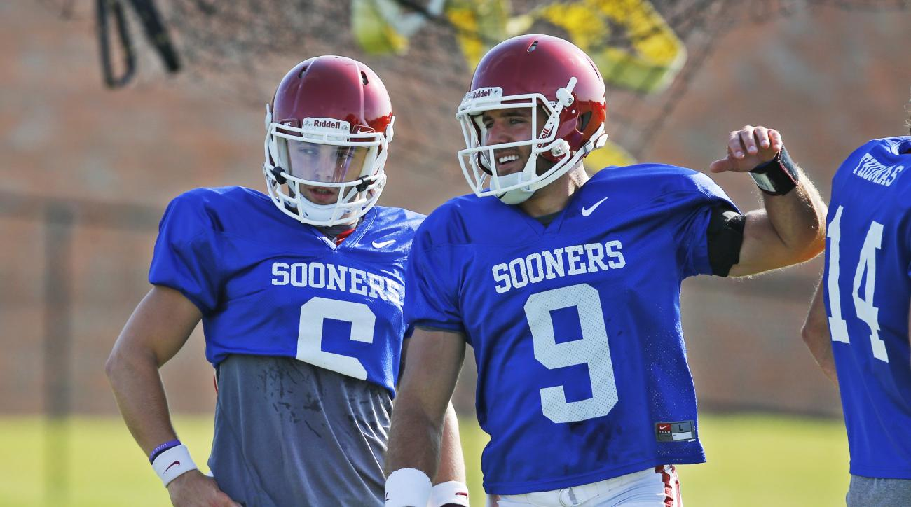 FILE - In this Aug. 10, 2015, file photo, Oklahoma quarterbacks Baker Mayfield, left, and Trevor Knight (9) talk during an Oklahoma NCAA college football practice in Norman, Okla. The Big 12 championship could be decided by backup quarterbacks _ as could