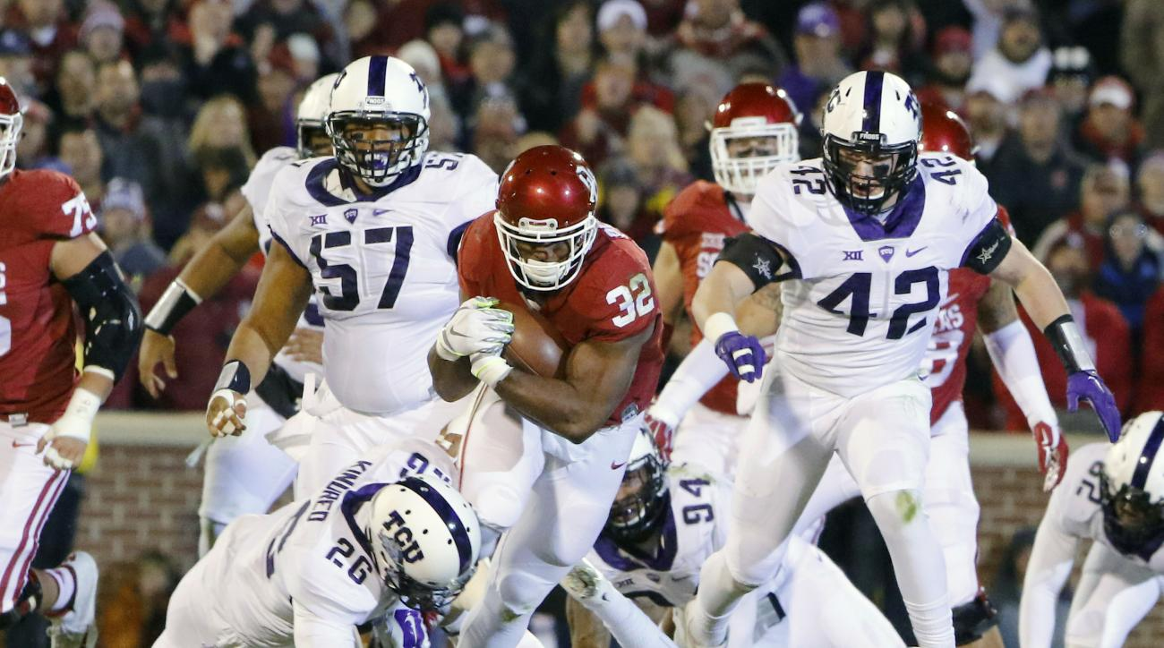FILE - In this Saturday, Nov. 21, 2015, file photo, Oklahoma running back Samaje Perine (32) carries between TCU safety Derrick Kindred (26) and TCU safety Nick Orr (18) during the first quarter of an NCAA college football game in Norman, Okla. Oklahoma p