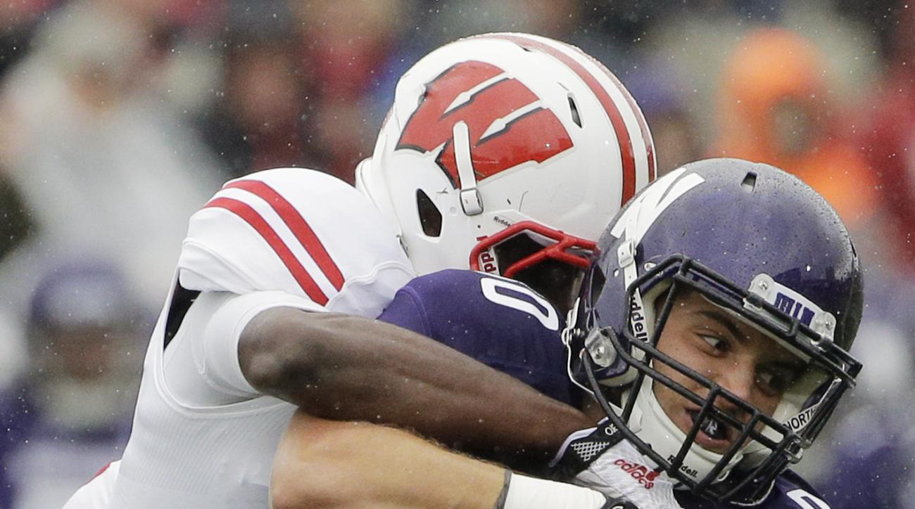 FILE - In this Oct. 4, 2015 file photo, Northwestern wide receiver Austin Carr (80) is tackled by Wisconsin safety Lubern Figaro during an NCAA college football game in Evanston, Ill. Northwestern faces Illinois Saturday, Nov. 28, 2015, in Chicago. The Wi