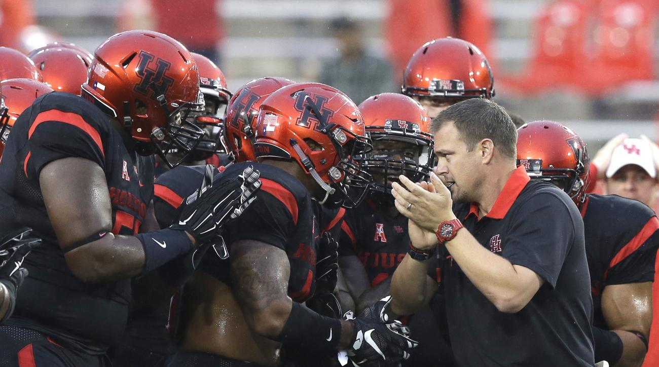 FILE - In this Oct. 31, 2015, file photo, Houston coach Tom Herman, right, encourages his players before an NCAA college football game against Vanderbilt in in Houston. After Connecticut ended Houston's unbeaten season last week, the Cougars head into Fri