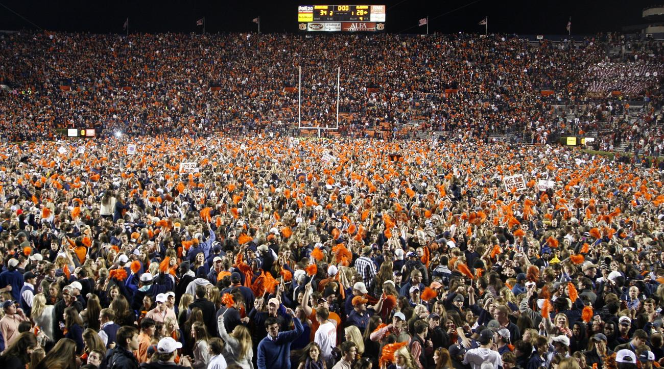 FILE - In this Saturday, Nov. 30, 2013, file photo, Auburn fans storm the field, blanketing it from goal line to goal line with a giddy mass of orange and blue after a win over Alabama during an NCAA college football game in Auburn, Ala. Alabama returns t