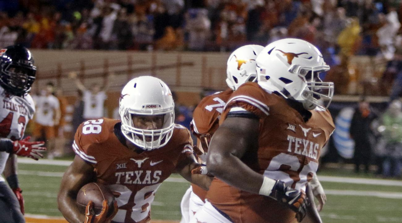 Texas running back Kirk Johnson (28) runs behind blockers Sedrick Flowers (66) and Taylor Doyle during the first half of an NCAA college football game against Texas Tech, Thursday, Nov. 26, 2015, in Austin, Texas. (AP Photo/Michael Thomas)