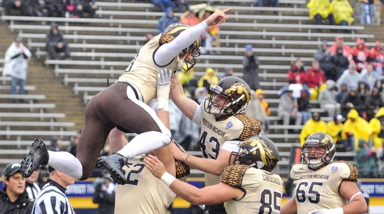 Western Michigan quarterback Tom Flacco , left, leaps in the air while celebrating with his teammates after running for a two-point conversion in the first quarter of an NCAA college football game against Toledo Friday, Nov. 27, 2015, in Toledo, Ohio. (AP