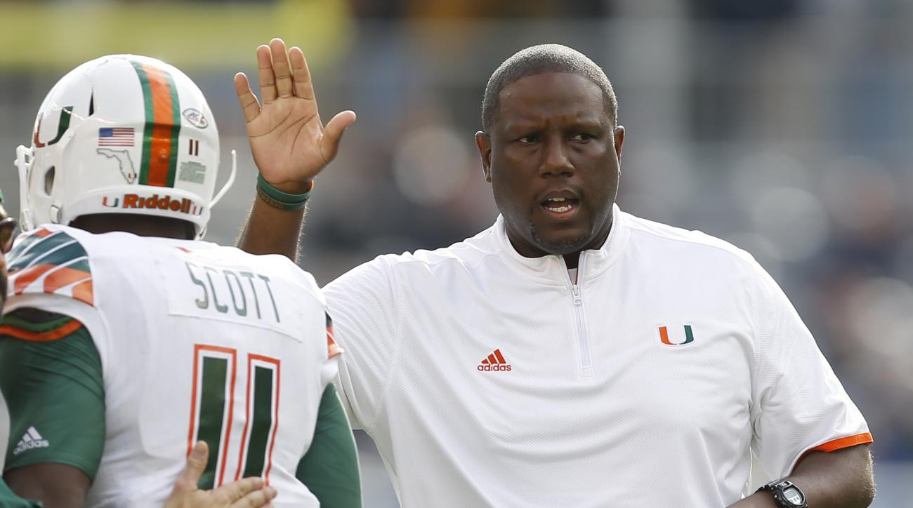 Miami head coach Larry Scott gets Miami wide receiver Rashawn Scott (11) after the team scored a touchdown in the first quarter of an NCAA college football game against Pittsburgh, Friday, Nov. 27, 2015, in Pittsburgh. Miami won 29-24. (AP Photo/Keith Sra