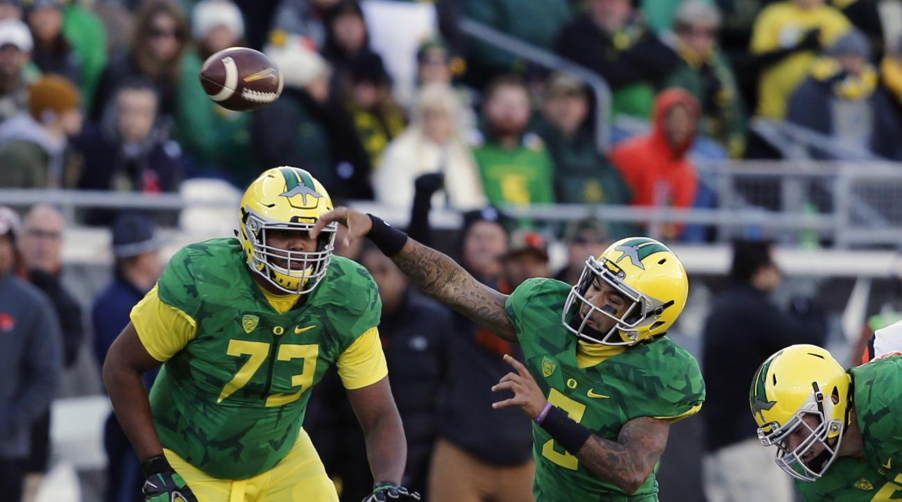 Oregon quarterback Vernon Adams, Jr. gets off a pass while being pressured by a pair of Oregon State defenders in the first half of an NCAA college football game, in Eugene Ore., on Friday, Nov. 27, 2015.  (AP Photo/Timothy J. Gonzalez)