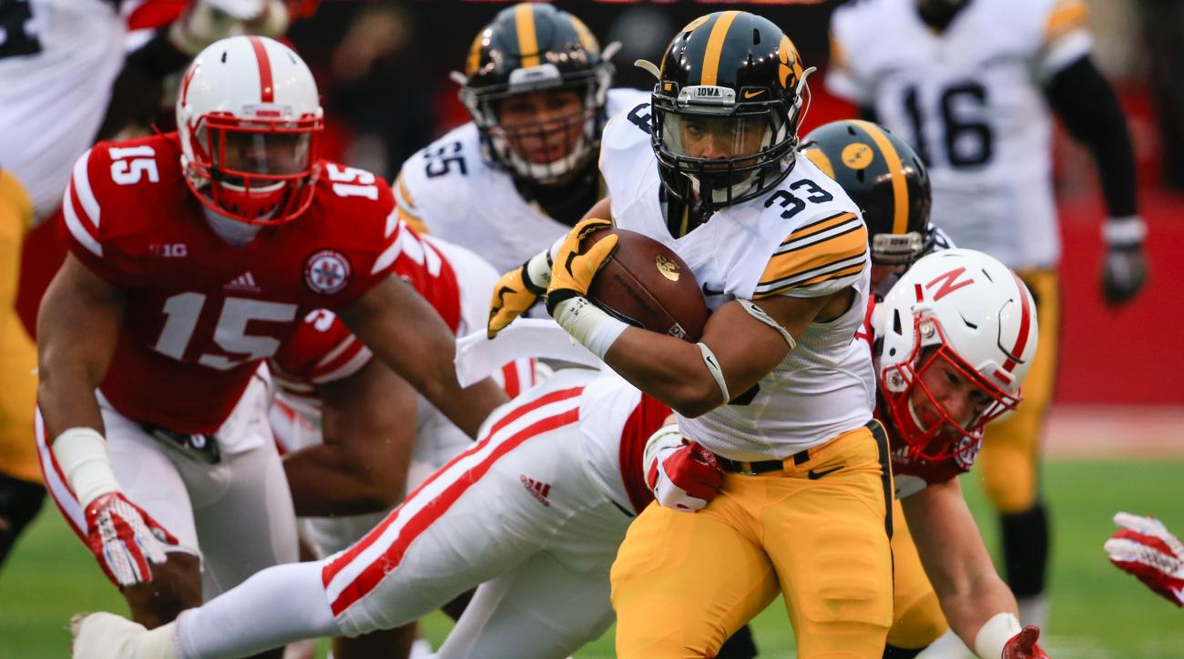 Iowa running back Jordan Canzeri (33) breaks a tackle by Nebraska linebacker Chris Weber (49) during the first half of an NCAA college football game in Lincoln, Neb., Friday, Nov. 27, 2015. (AP Photo/Nati Harnik)