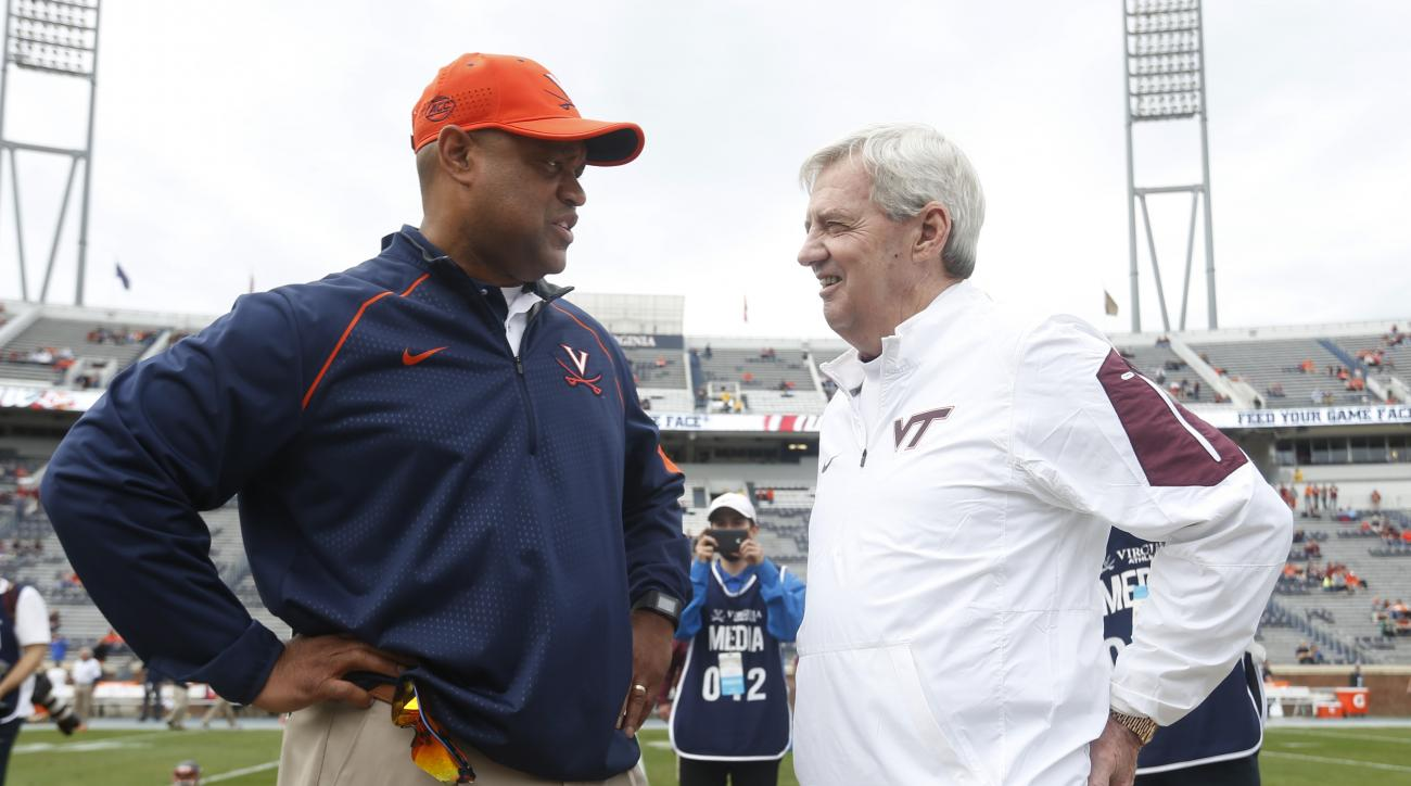 Virginia head coach Mike London, left, and Virginia Tech head coach Frank Beamer chat before an NCAA college football game in Charlottesville, Va., Saturday, Nov. 28, 2015. Beamer has announced his retirement at the end of the season.  (AP Photo/Steve Hel
