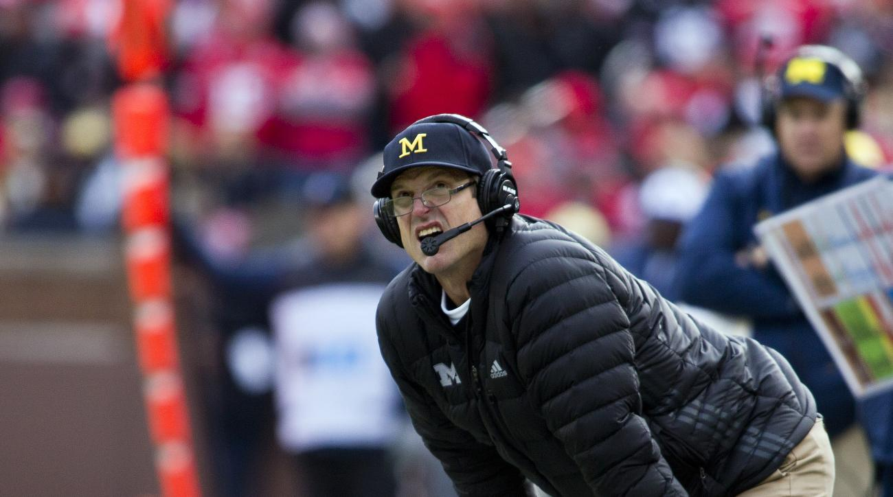 Michigan head coach Jim Harbaugh bends over on the sideline looking at the scoreboard in the fourth quarter of an NCAA college football game against Ohio State in Ann Arbor, Mich., Saturday, Nov. 28, 2015. Ohio State won 42-13. (AP Photo/Tony Ding)