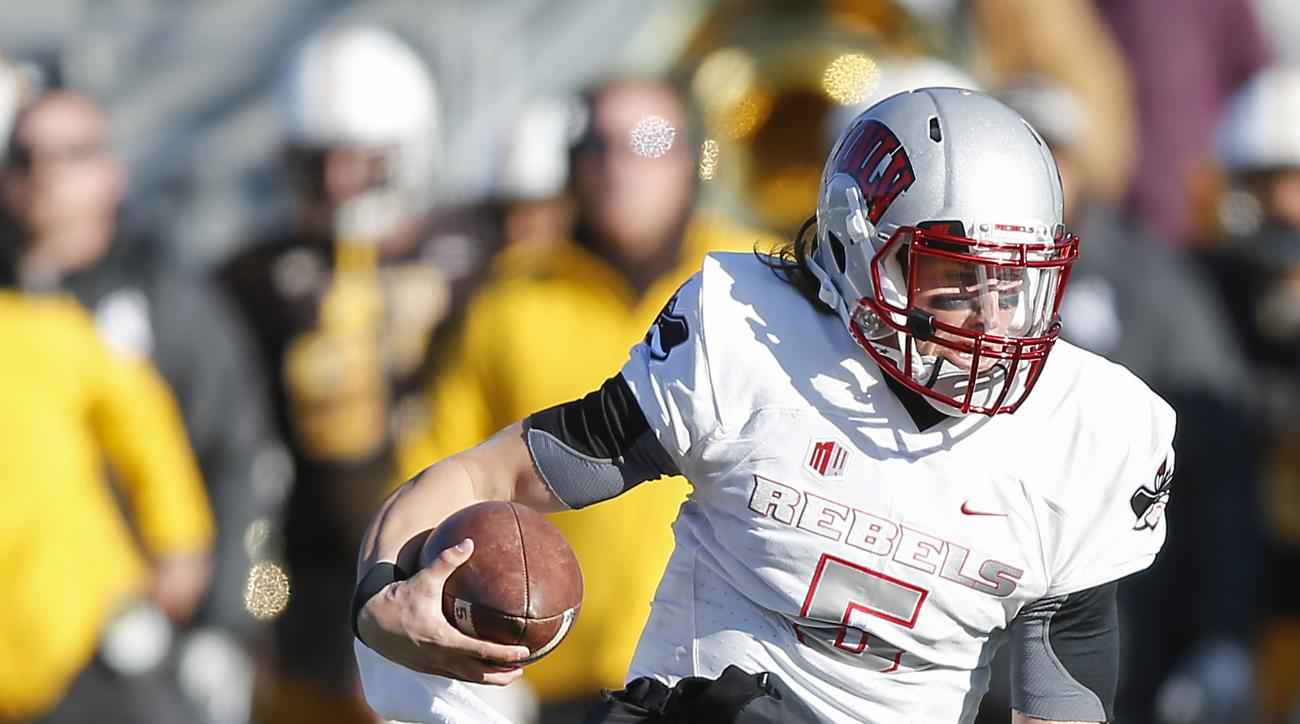 UNLV quarterback Blake Decker  runs past a Wyoming defender during the second quarter of an NCAA college football game, Saturday, Nov. 28, 2015, in Laramie, Wyo. (AP Photo/Michael Smith)