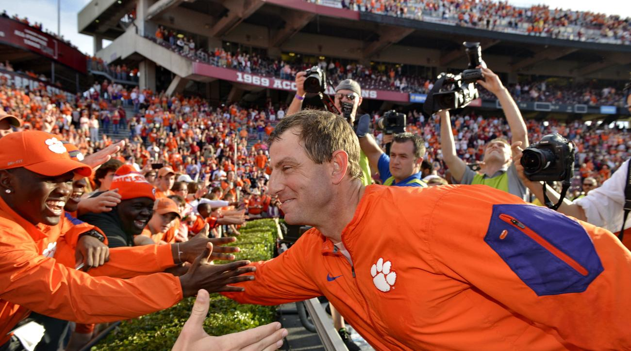 Clemson head coach Dabo Swinney celebrates with the fans after an NCAA college football game against South Carolina Saturday,  Nov. 28, 2015,  in Columbia,  S.C. Clemson won 37-32. (AP Photo/Richard Shiro)