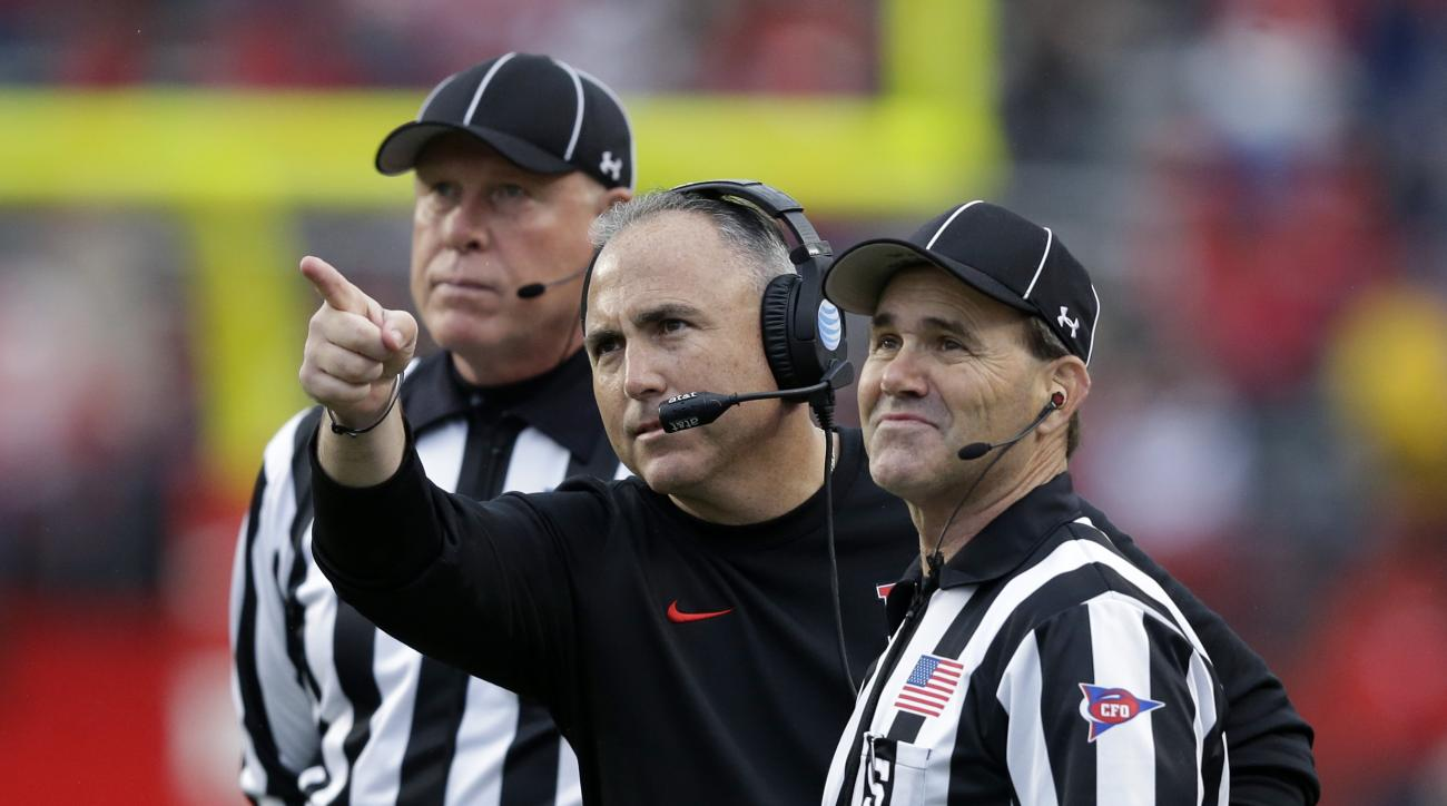 Rutgers head coach Kyle Flood, center, points out something on the sidelines to head linesman Kelly Saalfeld, left, and side judge Bobby Sagers, right, during the second half of an NCAA college football game against Maryland Saturday, Nov. 28, 2015, in Pi