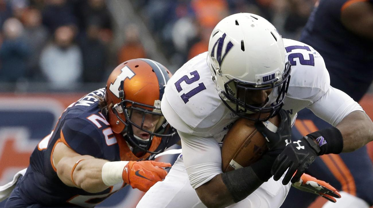 Northwestern running back Justin Jackson, right, runs past Illinois safety Clayton Fejedelem during the first half of an NCAA college football game, Saturday, Nov. 28, 2015, in Chicago. (AP Photo/Nam Y. Huh)