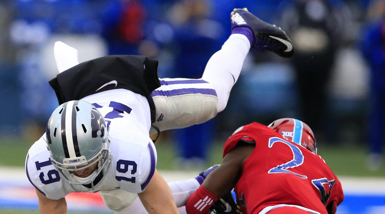 Kansas State wide receiver Kody Cook (19) catches a Joe Hubener pass while covered by Kansas safety Bazie Bates IV (24) during the first half of an NCAA college football game in Lawrence, Kan., Saturday, Nov. 28, 2015. (AP Photo/Orlin Wagner)