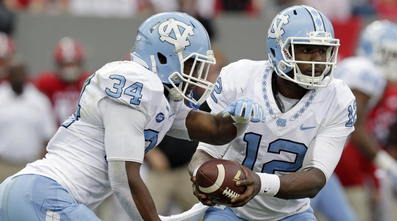 North Carolina quarterback Marquise Williams (12) hands the ball off to Elijah Hood (34) during the first half an NCAA college football game against North Carolina State in Raleigh, N.C., Saturday, Nov. 28, 2015. North Carolina won 45-34. (AP Photo/Gerry