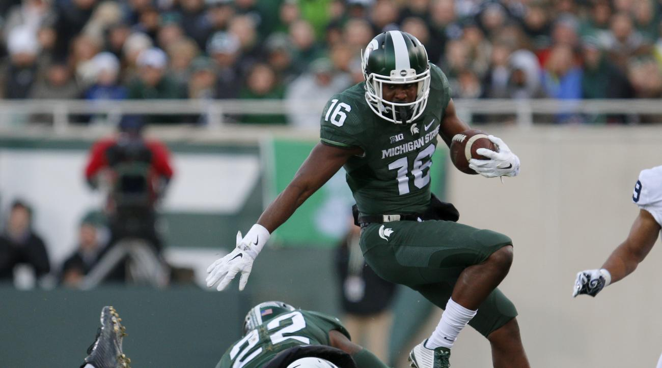 Michigan State's Aaron Burbridge (16) hurdles Penn State's Troy Reeder (42) and Michigan State's Delton Williams (22) during the first quarter of an NCAA college football game, Saturday, Nov. 28, 2015, in East Lansing, Mich. Michigan State won 55-16. (AP