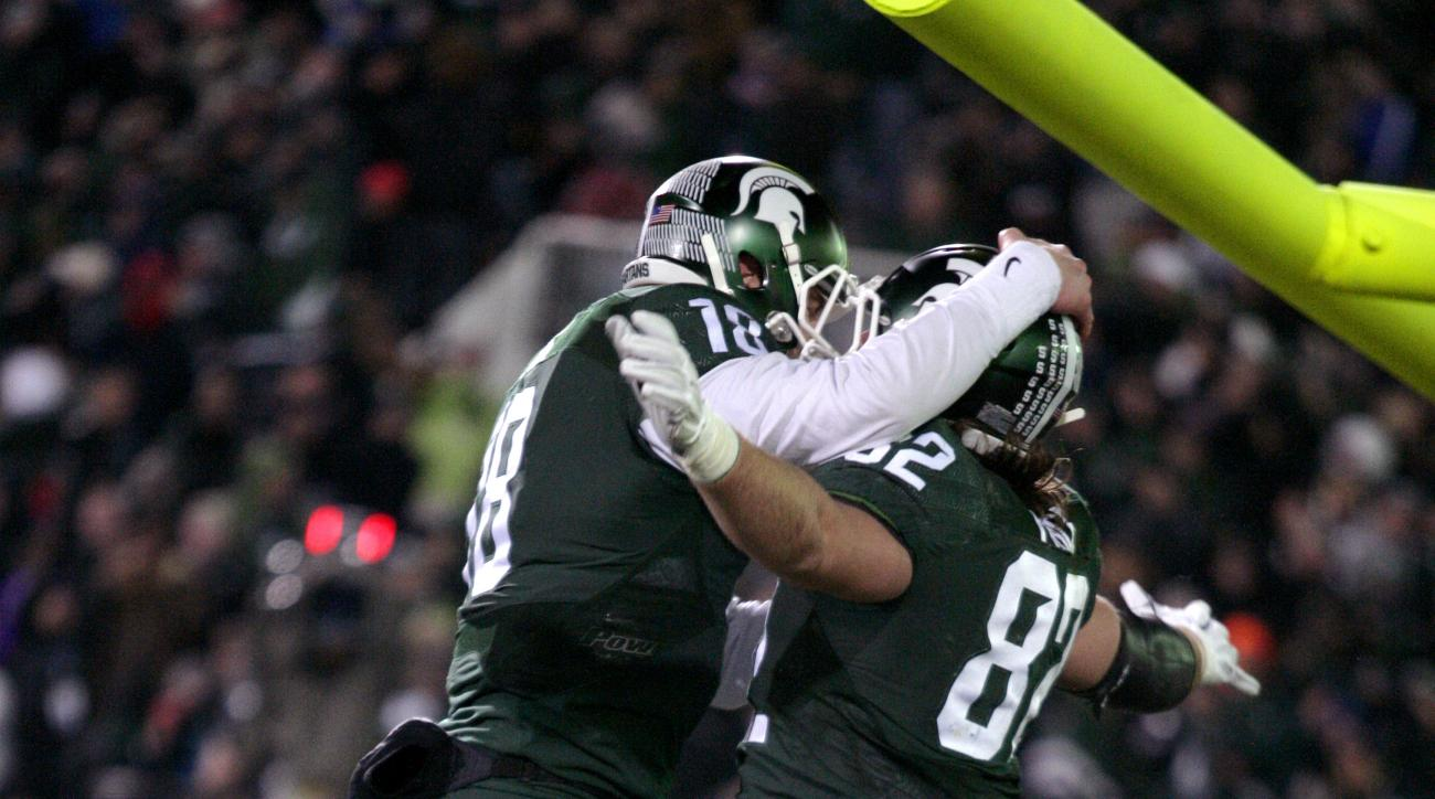 Michigan State quarterback Connor Cook, left, and tight end Josiah Price celebrate Price's touchdown reception against Penn State during the third quarter of an NCAA college football game, Saturday, Nov. 28, 2015, in East Lansing, Mich. Michigan State won