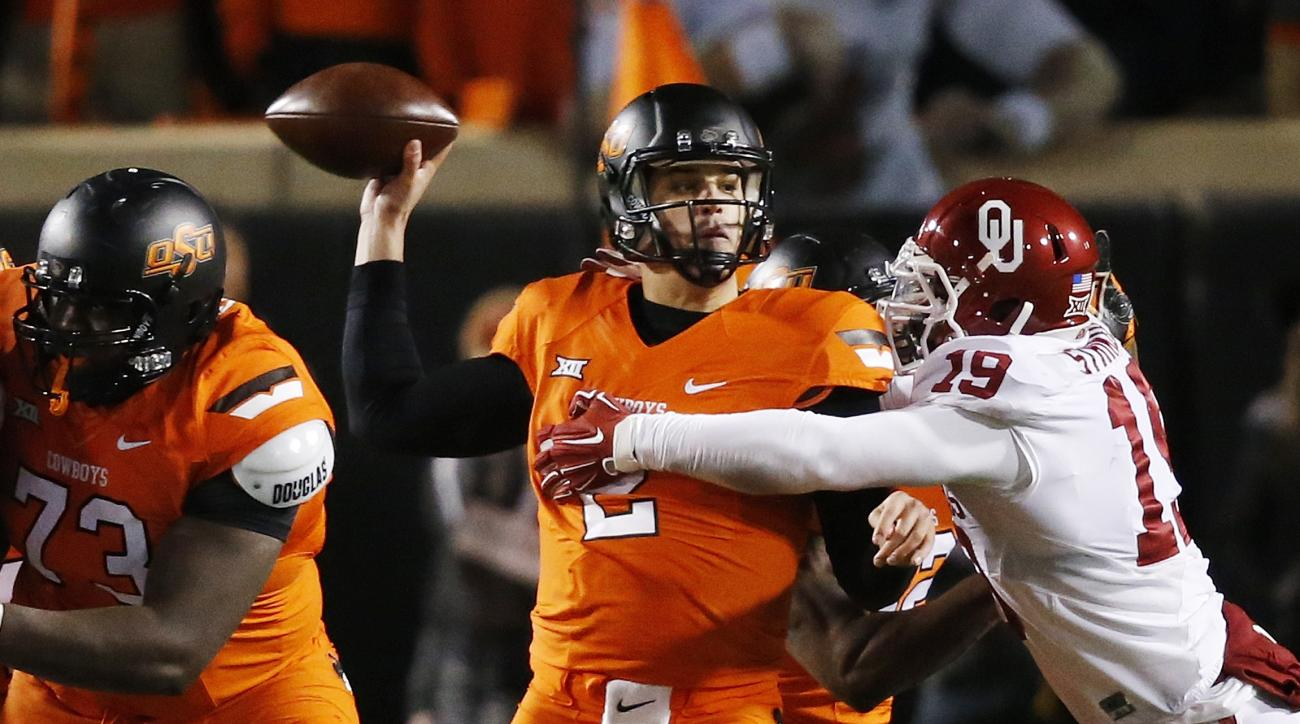 Oklahoma State quarterback Mason Rudolph (2) throws an interception under pressure from Oklahoma linebacker Eric Striker (19) in the second quarter of an NCAA college football game in Stillwater, Okla., Saturday, Nov. 28, 2015. (AP Photo/Sue Ogrocki)
