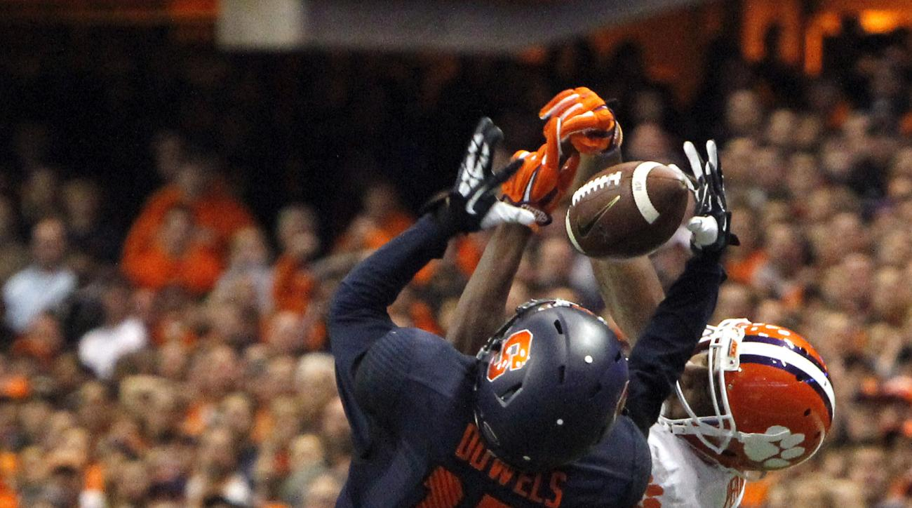 FILE - In this Nov. 14, 2015, file photo, Syracuse's Juwan Dowels, left, and Clemson's Charone Peake, right, battle for a pass in the third quarter of an NCAA college football game in Syracuse, N.Y. Dowels intercepted the pass. Turnovers is an area of con