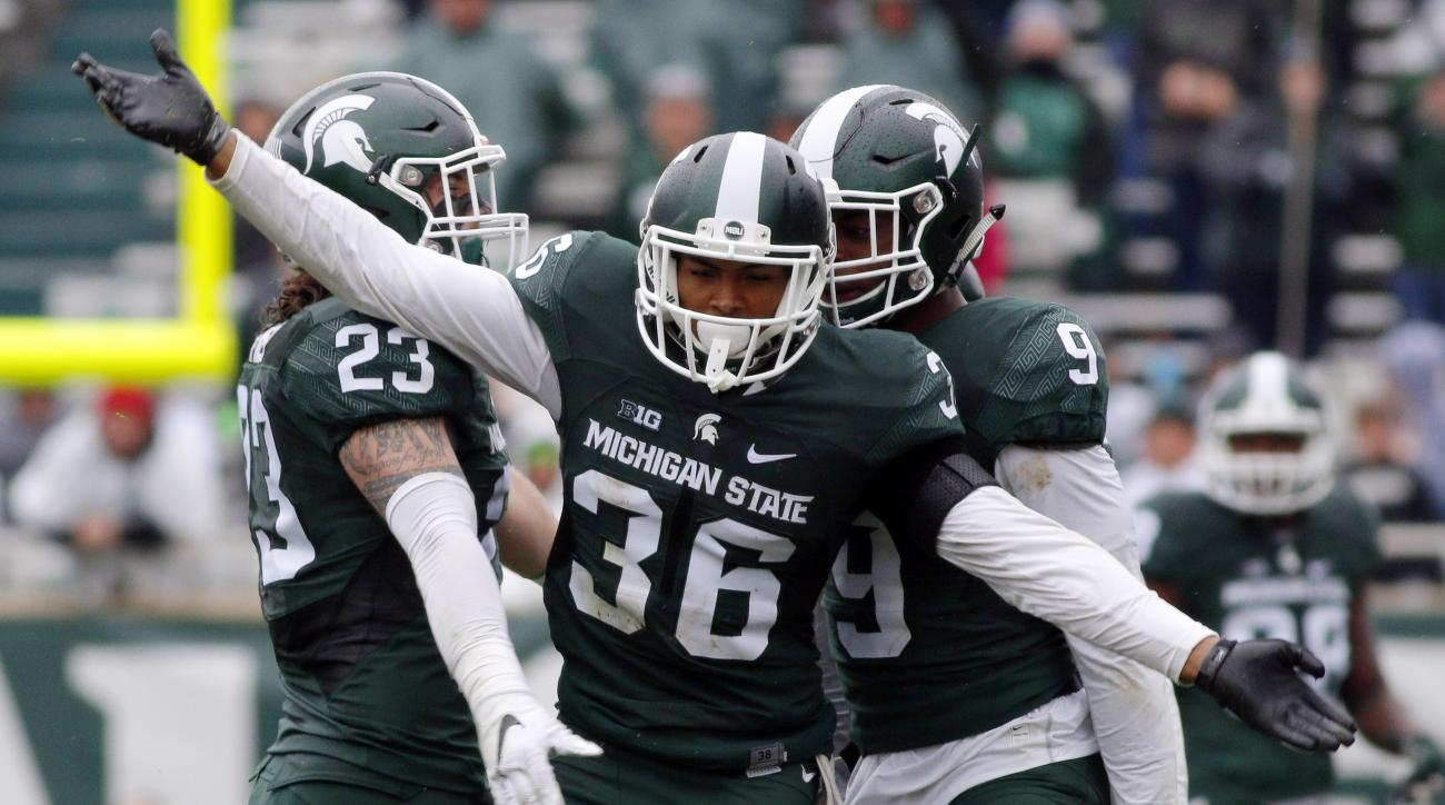 FILE - In this Oct. 3, 2015, file photo,Michigan State's Arjen Colquhoun (36), Chris Frey (23) and Montae Nicholson celebrate a play during the fourth quarter of an NCAA college football game against Purdue in East Lansing, Mich. About a month ago, Michig