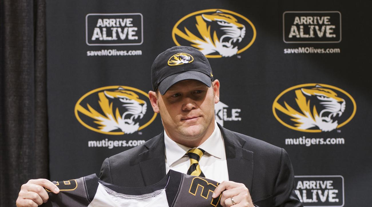 New Missouri NCAA college football coach Barry Odom holds up a uniform at his introductory press conference Friday, Dec. 4, 2015, in Columbia, Mo.  (AP Photo/L.G. Patterson)