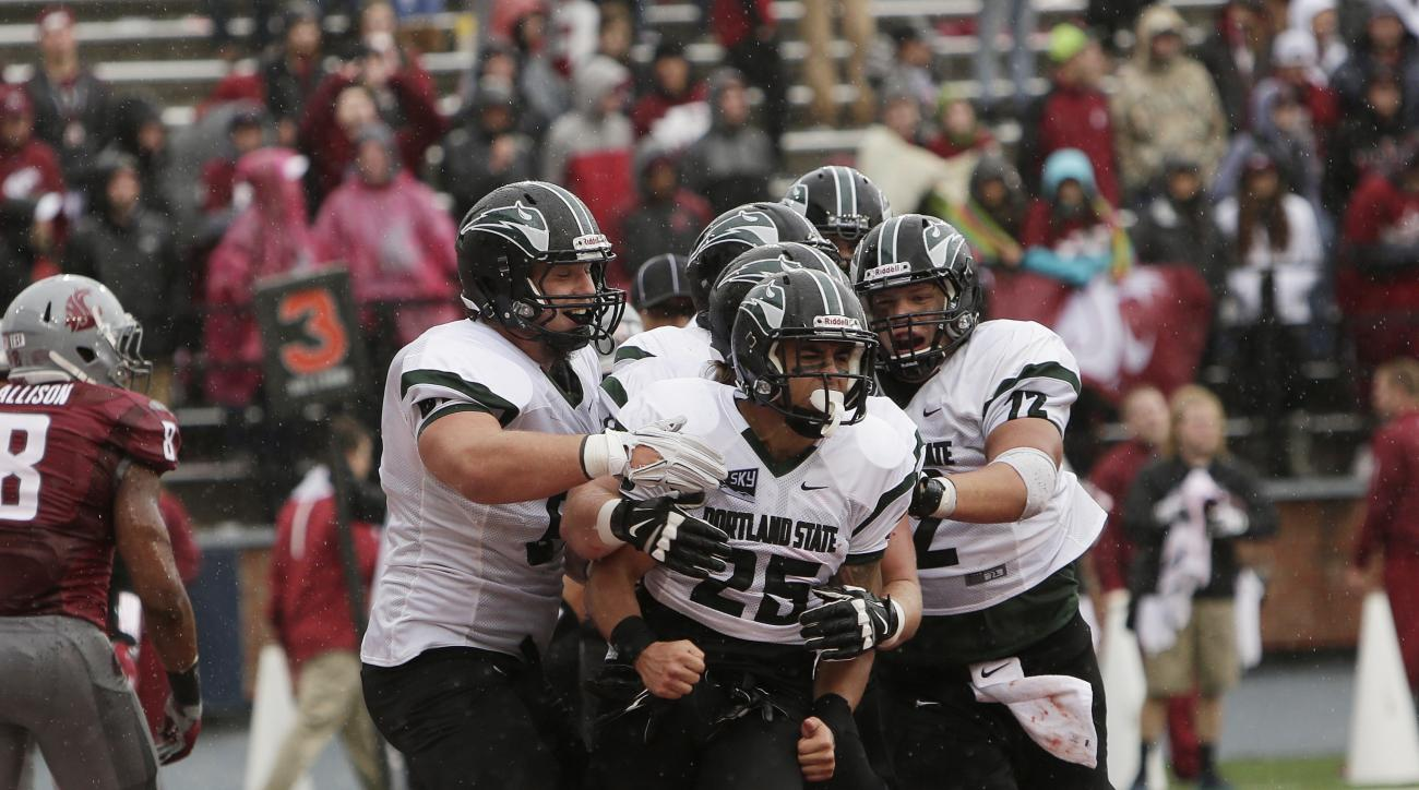 FILE - In this Sept. 5, 2015, file photo, Portland State running back Nate Tago (25) celebrates with teammates, including offensive lineman Chad Bach (72) and offensive lineman Kyle Smith, left, after scoring a touchdown during the second half of an NCAA