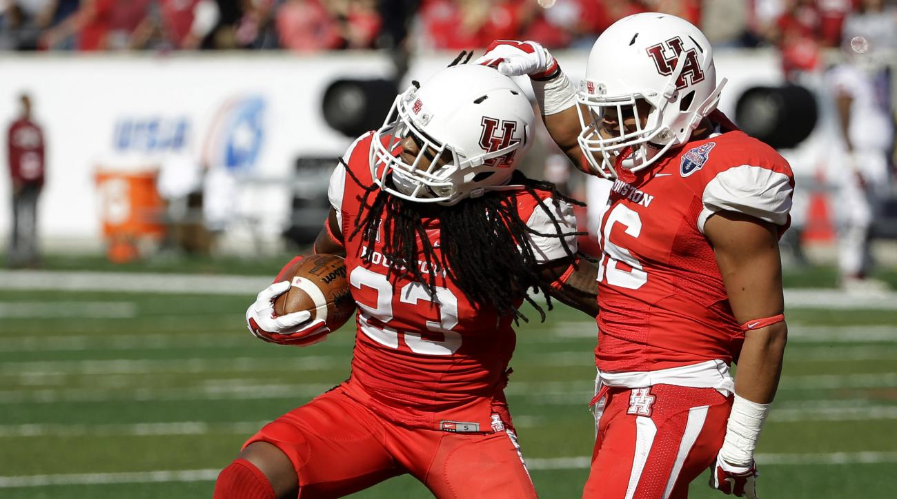 Houston safety Trevon Stewart (23) celebrates with safety Adrian McDonald (16) after recovering a fumble by Temple during the first quarter of the American Athletic Conference championship football game, Saturday, Dec. 5, 2015, in Houston. (AP Photo/David