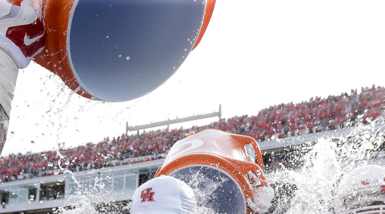 Houston coach Tom Herman is dunked with water during the closing seconds of the American Athletic Conference championship football game against Temple, Saturday, Dec. 5, 2015, in Houston. Houston won 24-13. (AP Photo/David J. Phillip)