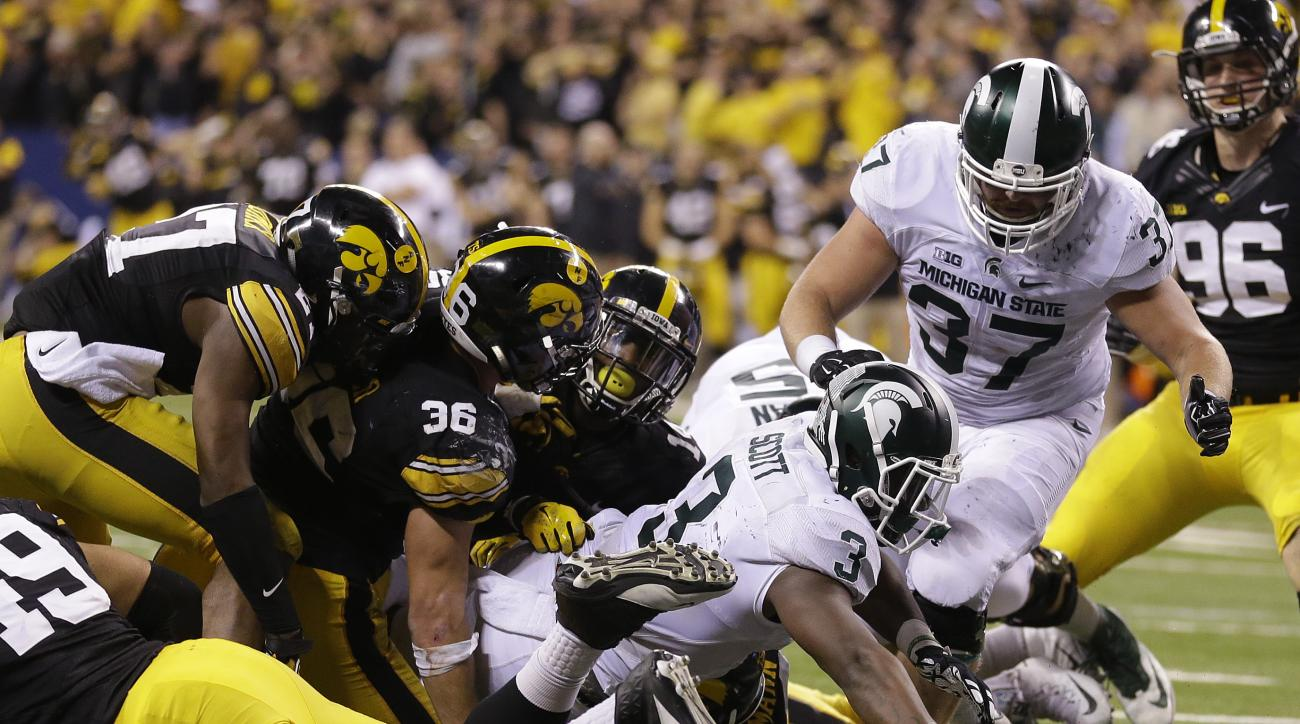 Michigan State's LJ Scott (3) runs for a 1-yard touchdown during the second half of the Big Ten championship NCAA college football game against Iowa, Saturday, Dec. 5, 2015, in Indianapolis. (AP Photo/Michael Conroy)