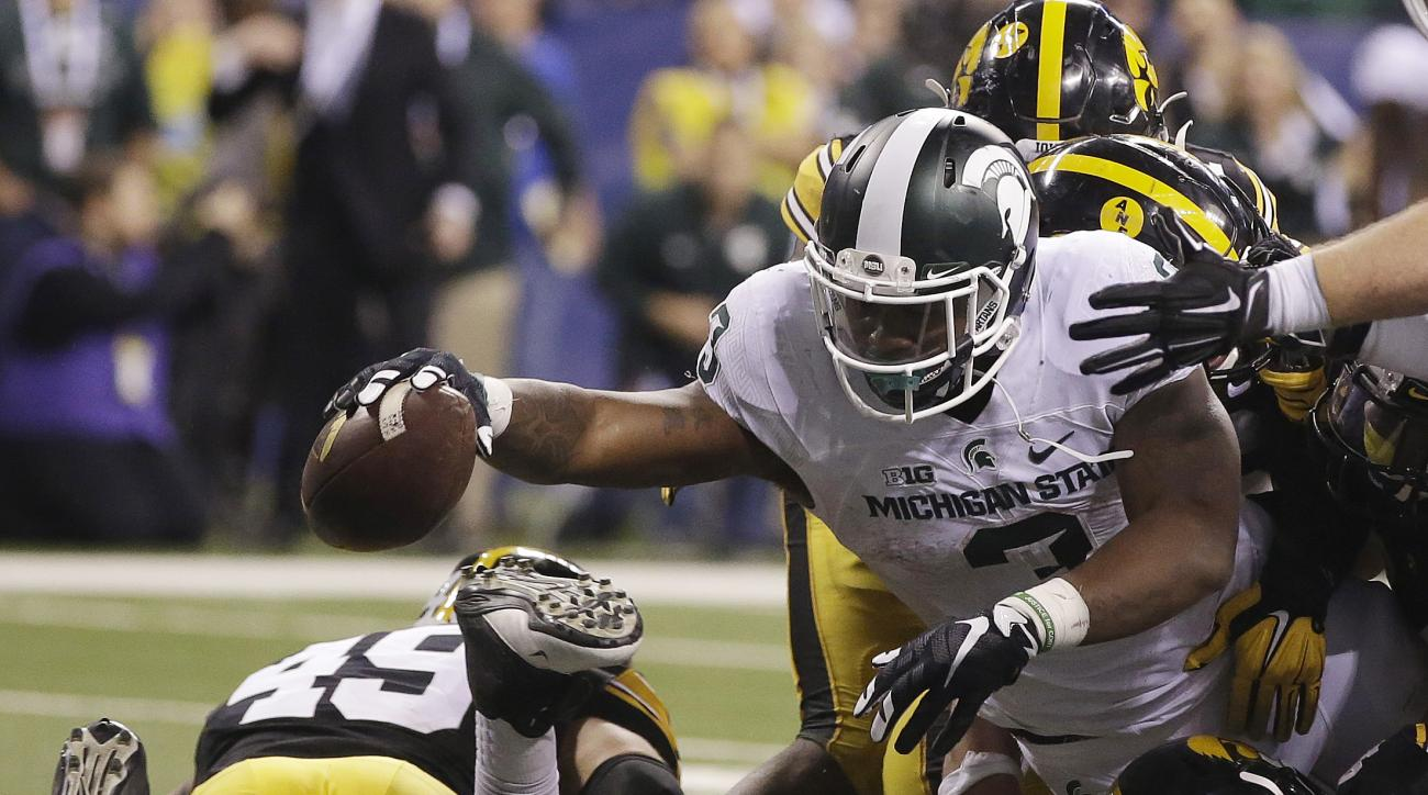 Michigan State's LJ Scott (3) runs for a 1-yard touchdown during the second half of the Big Ten championship NCAA college football game against Iowa, Saturday, Dec. 5, 2015, in Indianapolis. (AP Photo/Darron Cummings)