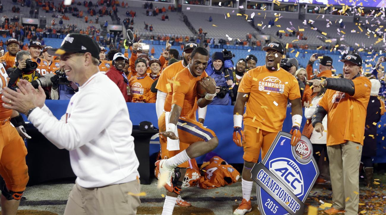 Clemson quarterback Deshaun Watson holds a football as coach Dabo Swinney celebrates after Clemson defeated North Carolina 45-37 in the Atlantic Coast Conference championship NCAA college football game in Charlotte, N.C., early Sunday, Dec. 6, 2015. (AP P