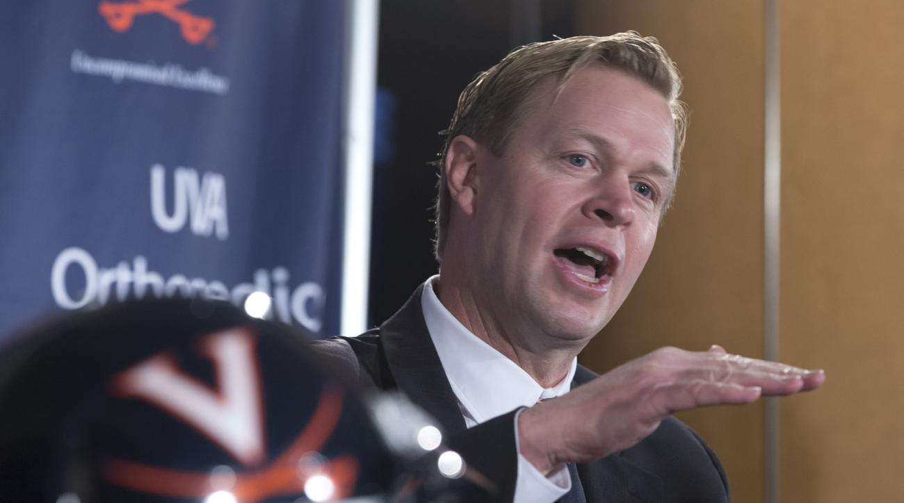 New University of Virginia NCAA college head football coach, Bronco Mendenhall, smiles during a news conference at the school  in Charlottesville, Va., Monday, Dec. 7, 2015.  Mendenhall takes over after his current team Brigham Young University competes i